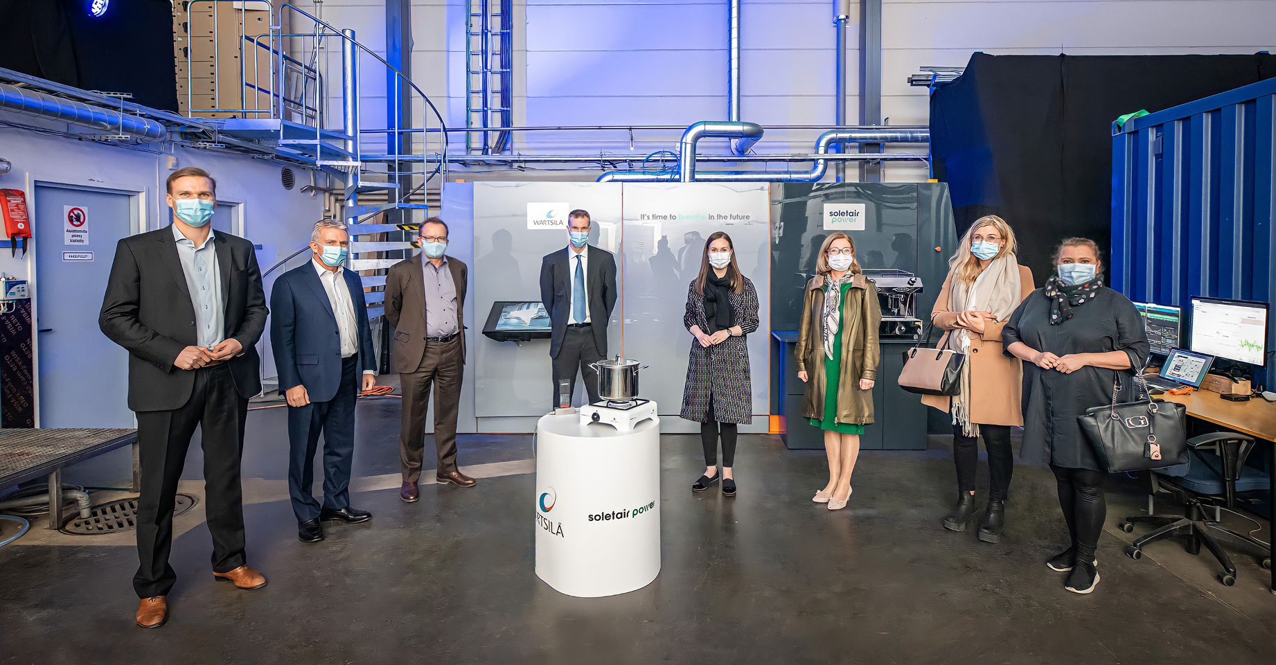 8 people standing and Sanna Marin Visits Soletair Power Factory